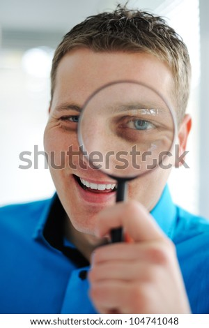Portrait of a young business man with magnifying glass - stock photo