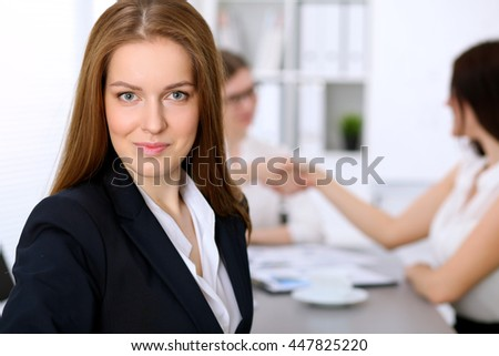 Portrait of a young business woman against a group of business people at  meeting.