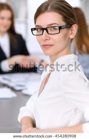 Portrait of a young business woman against a group of business people at  meeting. - stock photo