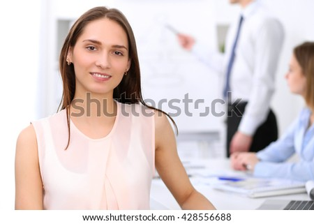 Portrait of a young business woman at meeting.