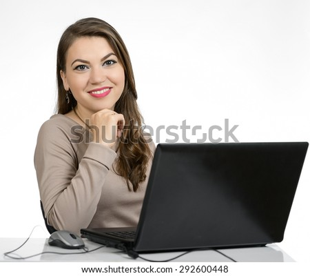 Portrait of a young business woman sitting at a laptop on a white background.