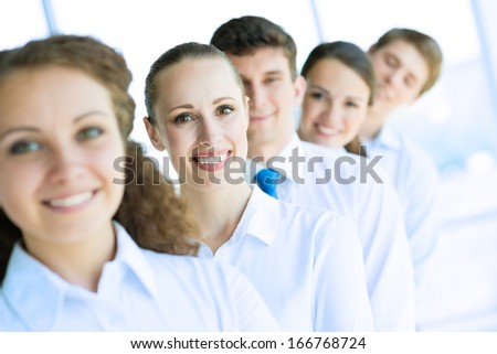 portrait of a young business woman standing in line with colleagues, concept of teamwork - stock photo