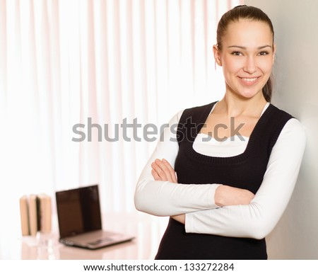 Portrait of a young business woman standing in office - stock photo
