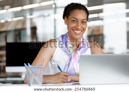 Portrait of a young business woman working on a laptop in a office