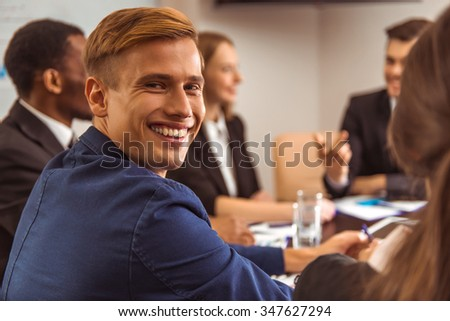 Portrait of a young businessman at a conference in the office on the background of her colleagues - stock photo