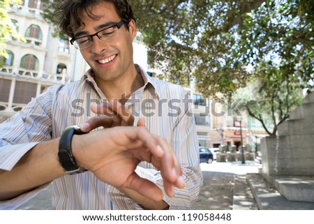 Portrait of a young businessman checking his watch while standing in a classic city exterior.