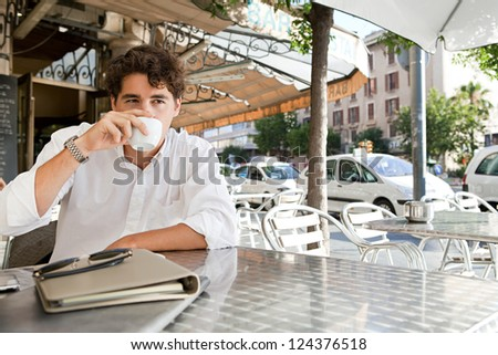 Portrait of a young businessman drinking coffee while sitting outdoors in a coffee shop terrace table with office buildings around in the city. - stock photo