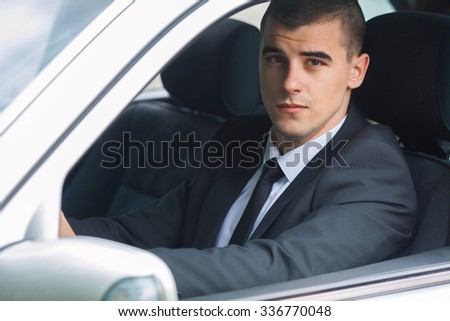 Portrait of a young businessman driving a car