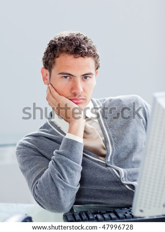 Portrait of a young businessman getting bored at work in the office - stock photo