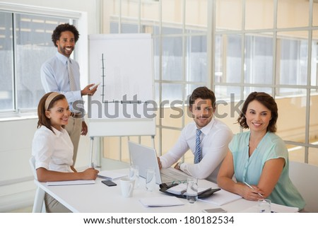 Portrait of a young businessman giving presentation to colleagues in a bright office - stock photo