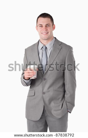 Portrait of a young businessman holding a cup of tea against a white background