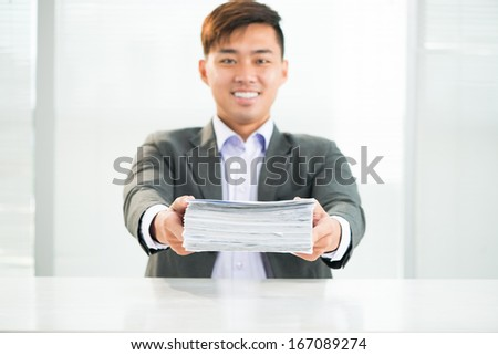 Portrait of a young businessman holding a heap of documents before deadline  - stock photo