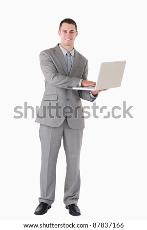 Portrait of a young businessman holding a laptop against a white background