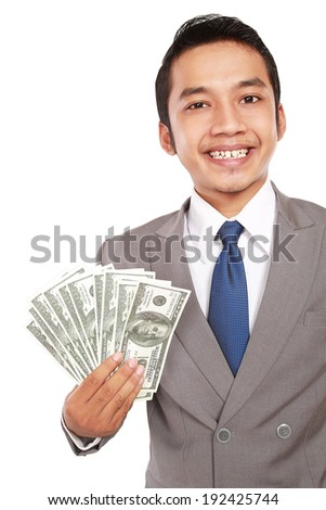 Portrait of a young businessman holding money, isolated on white background