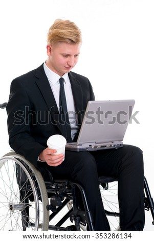 portrait of a young businessman in a wheelchair with computer and coffee mug - stock photo