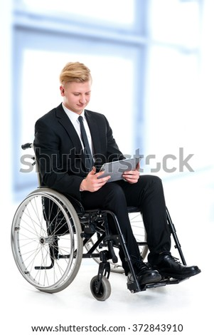 portrait of a young businessman in a wheelchair with tablet computer  - stock photo