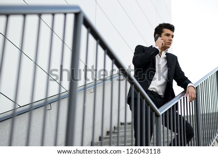 Portrait of a young businessman in an office building talking on the phone - stock photo