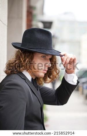 Portrait of a young businessman in designer hat, urban background
