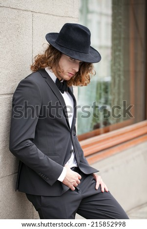 Portrait of a young businessman in designer hat, urban background  - stock photo