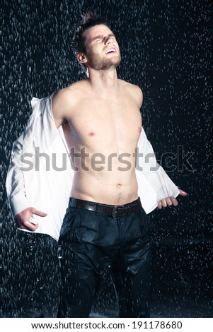 Portrait of a young businessman in the rain - stock photo