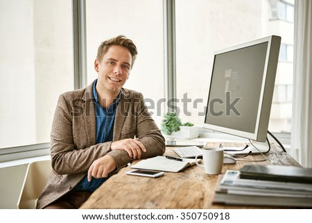 Portrait of a young businessman looking at the camera with a positive expression and looking relaxed and confident - stock photo