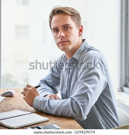 Portrait of a young businessman looking seriously at the camera while sitting in his office at his desk  - stock photo