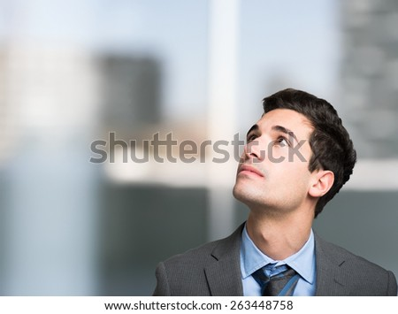 Portrait of a young businessman looking up in his office - stock photo