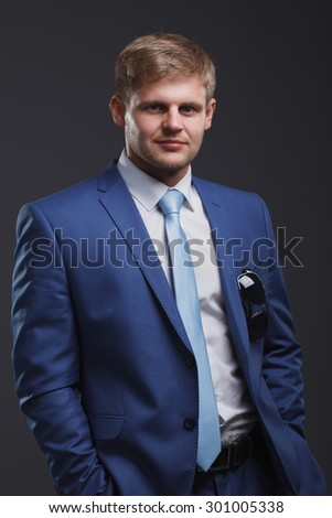 Portrait of a young businessman on a gray background