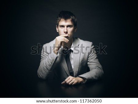 Portrait of a young businessman on black background - stock photo