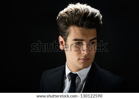Portrait of a young businessman, on black background - stock photo