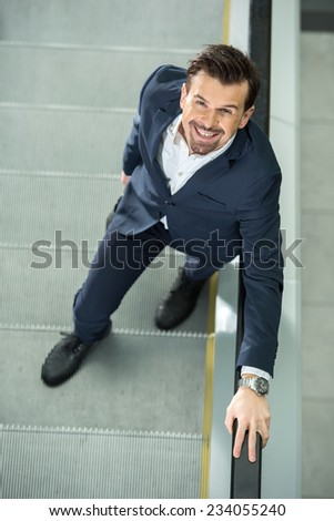 Portrait of a young businessman on stairs. View from above. - stock photo