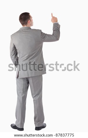 Portrait of a young businessman pointing at something against a white background - stock photo