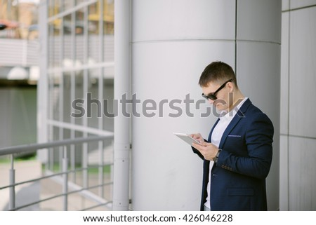 Portrait of a young businessman seeing on his tablet pc on the street. Man in blue suit with dark sunglasses. - stock photo