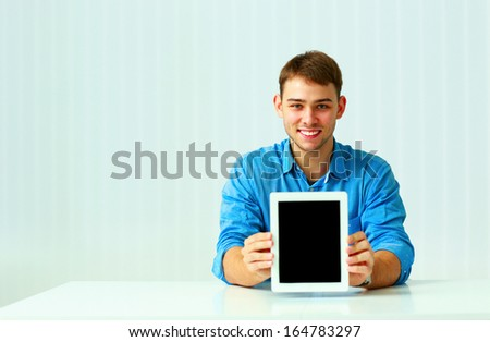 Portrait of a young businessman shows the tablet computer screen at office