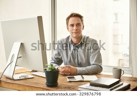 Portrait of a young businessman sitting at his desk in a calm and confident manner and looking seriously at the camera  - stock photo