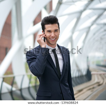 Portrait of a young businessman smiling and talking on the phone at station - stock photo