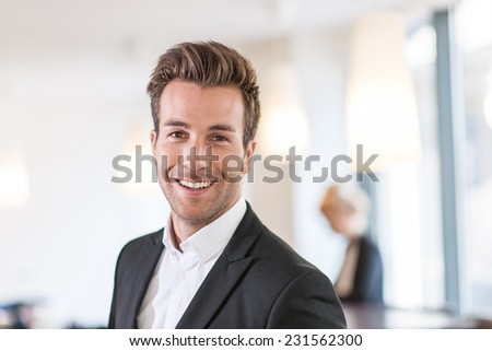 Portrait of a young businessman   standing at office, female colleague in the background - stock photo