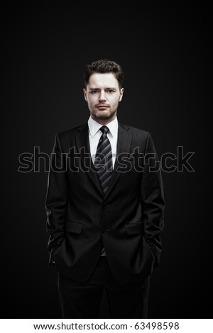 portrait of a young businessman standing with his hands in the pockets. - stock photo