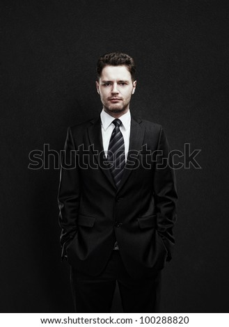 Portrait of a young businessman standing with his hands in the pockets. Young handsome man  looking confident. On a black background - stock photo