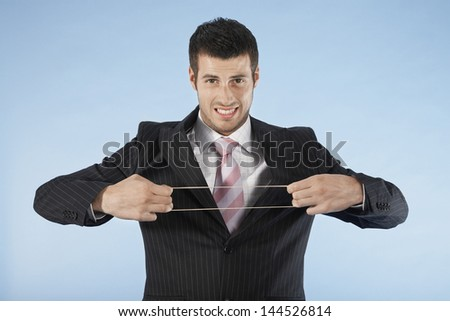 Portrait of a young businessman stretching rubber band on blue background - stock photo