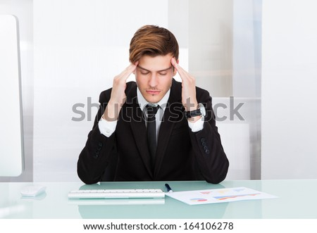 Portrait Of A Young Businessman Suffering From Headache In Office - stock photo