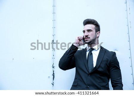Portrait of a young businessman talking on his smartphone on the street - stock photo