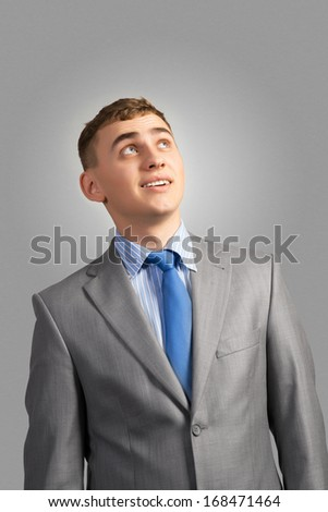portrait of a young businessman thinking and looking up on gray background - stock photo