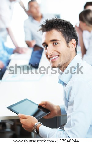 Portrait of a young  businessman using his digital tablet, colleagues in the background