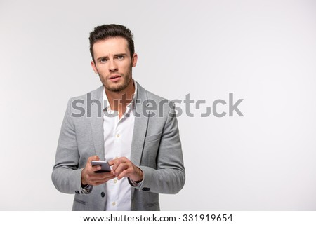 Portrait of a young businessman using smartphone and looking at camera isolated on a white background - stock photo