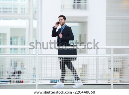 Portrait of a young businessman walking and talking on mobile phone - stock photo