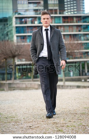 Portrait of a young businessman walking outdoors - stock photo