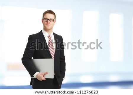 Portrait of a young businessman with a laptop smiling in his office - stock photo