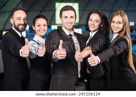 Portrait of a young businessman with business team in modern conference hall. - stock photo