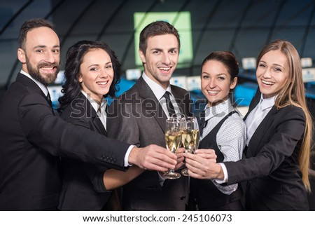 Portrait of a young businessman with business team in modern conference hall with glasses of champagne.